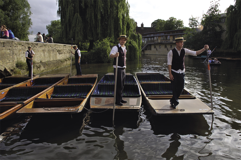 Four chauffeurs waiting on the back of their punts before taking guests to a may ball