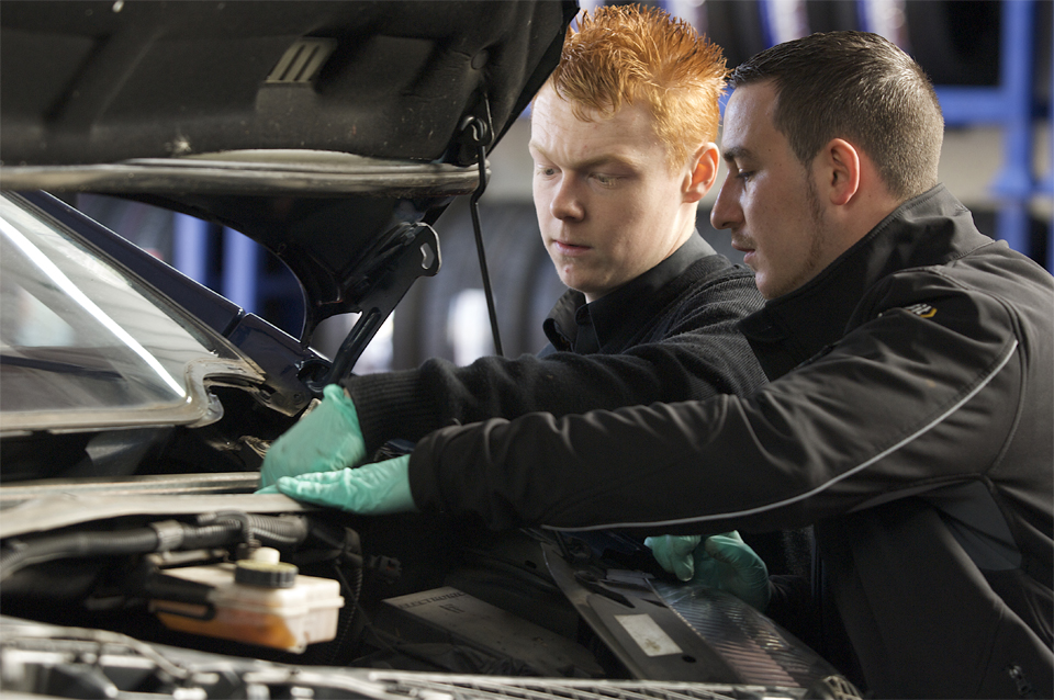 Two mechanics work on an engine at the Cambridge branch of Kall Kwik
