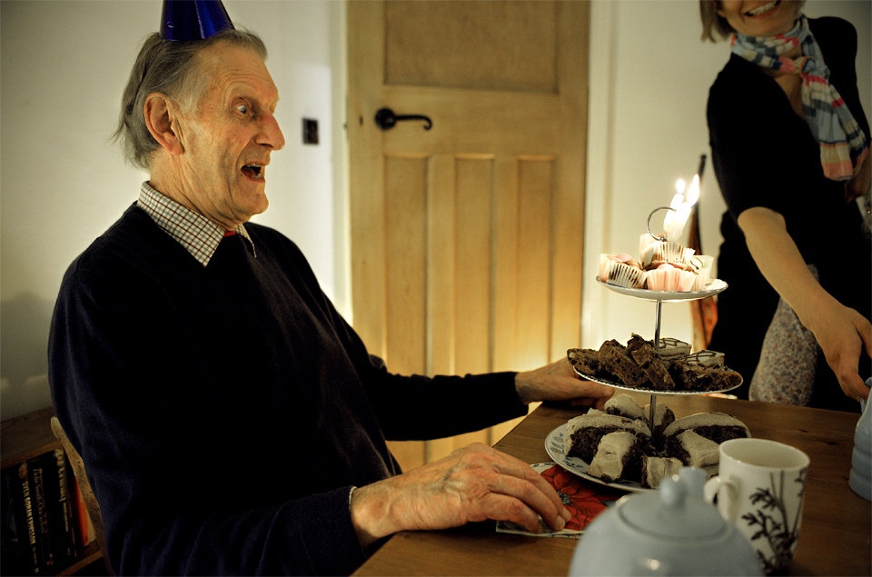 Suprised 80 year old at the arrival of his cakes